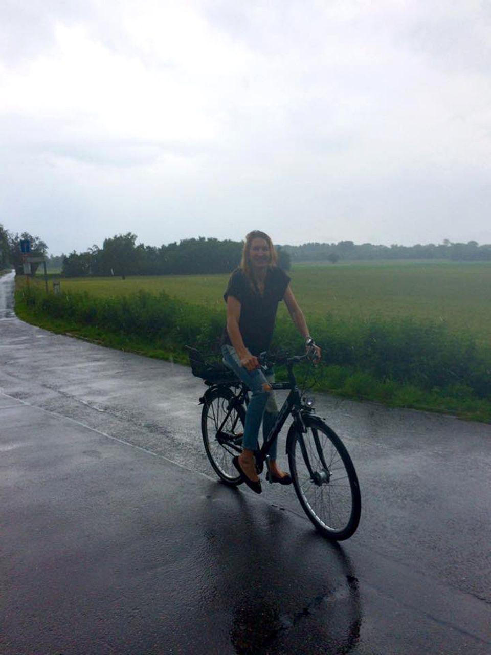 Steffi Graf kommt mit ihrem Rad in einen Regenschauer, nimmt es aber bei den sommerlichen Temperaturen gelassen.