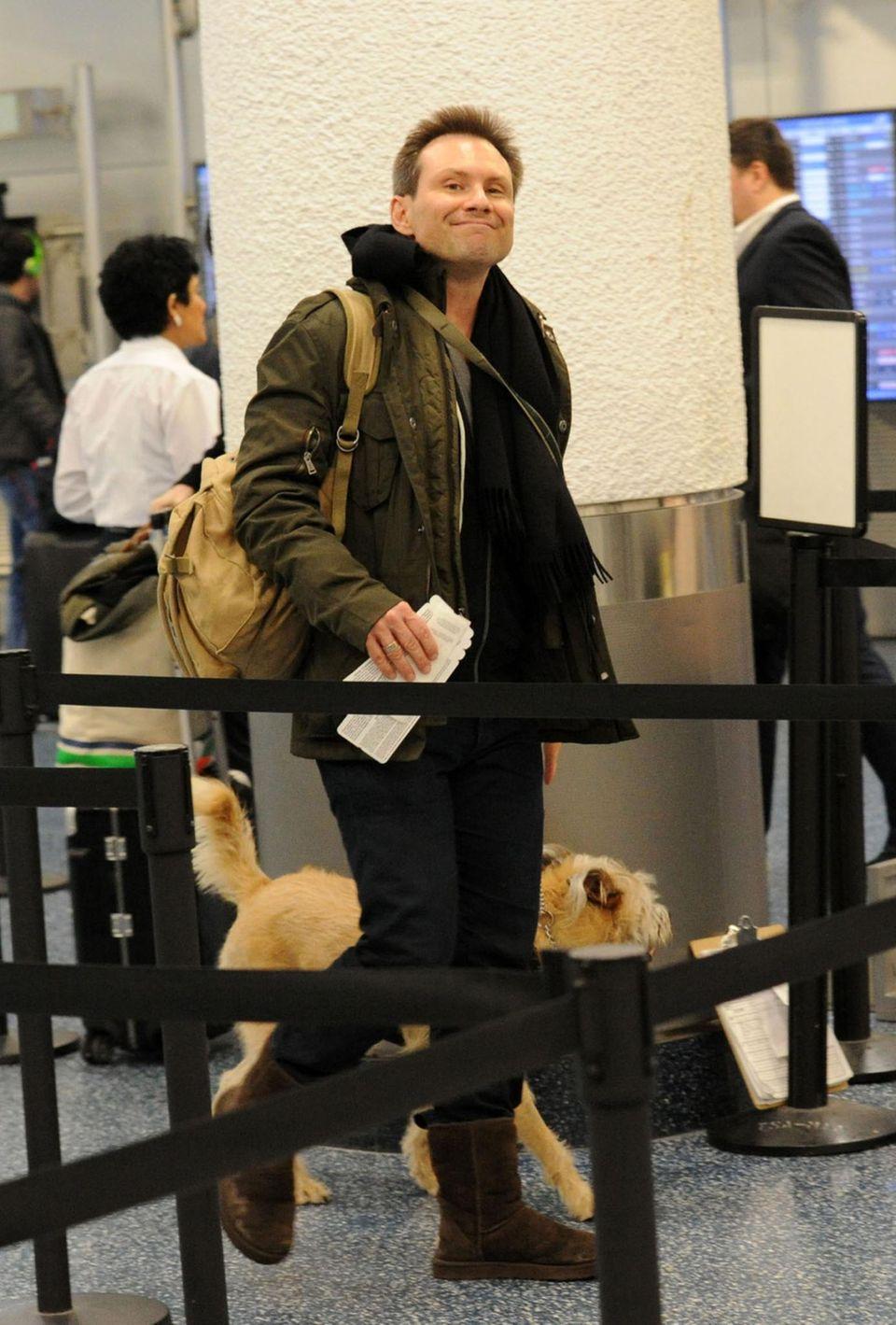 Christian Slater passiert mit Hund und Rucksack die Sicherheitskontrolle des Flughafens in Miami.