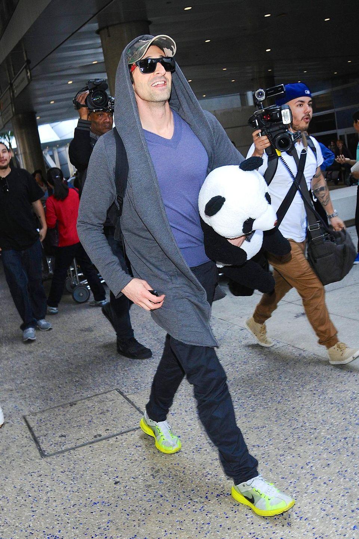 Zeigt Adrien Brody das Kind im Mann oder ist der kuschelige Pandabär, mit dem der Schauspieler in Kalifornien aus dem Flugzeug steigt, ein Mitbringsel für einen jungen Freund?