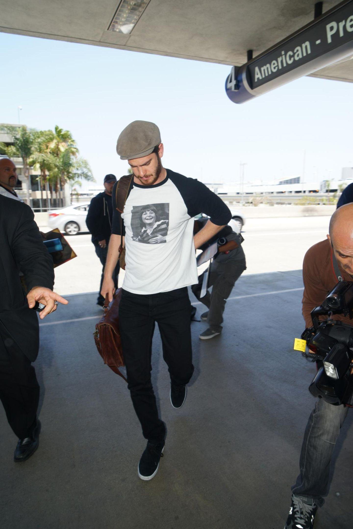 Andrew Garfield kommt bei strahlendem Sonnenschein und mit einem Kinderbild von Michael J. Fox auf dem T-Shirt am Flughafen von Los Angeles an.