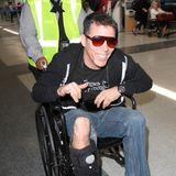 """Im Rollstuhl mit gebrochenem Bein und bester Laune: Am Flughafen von Los Angeles """"LAX"""" wird """"Jackass""""-Star Steve-O von einer Angestellten angeschoben."""