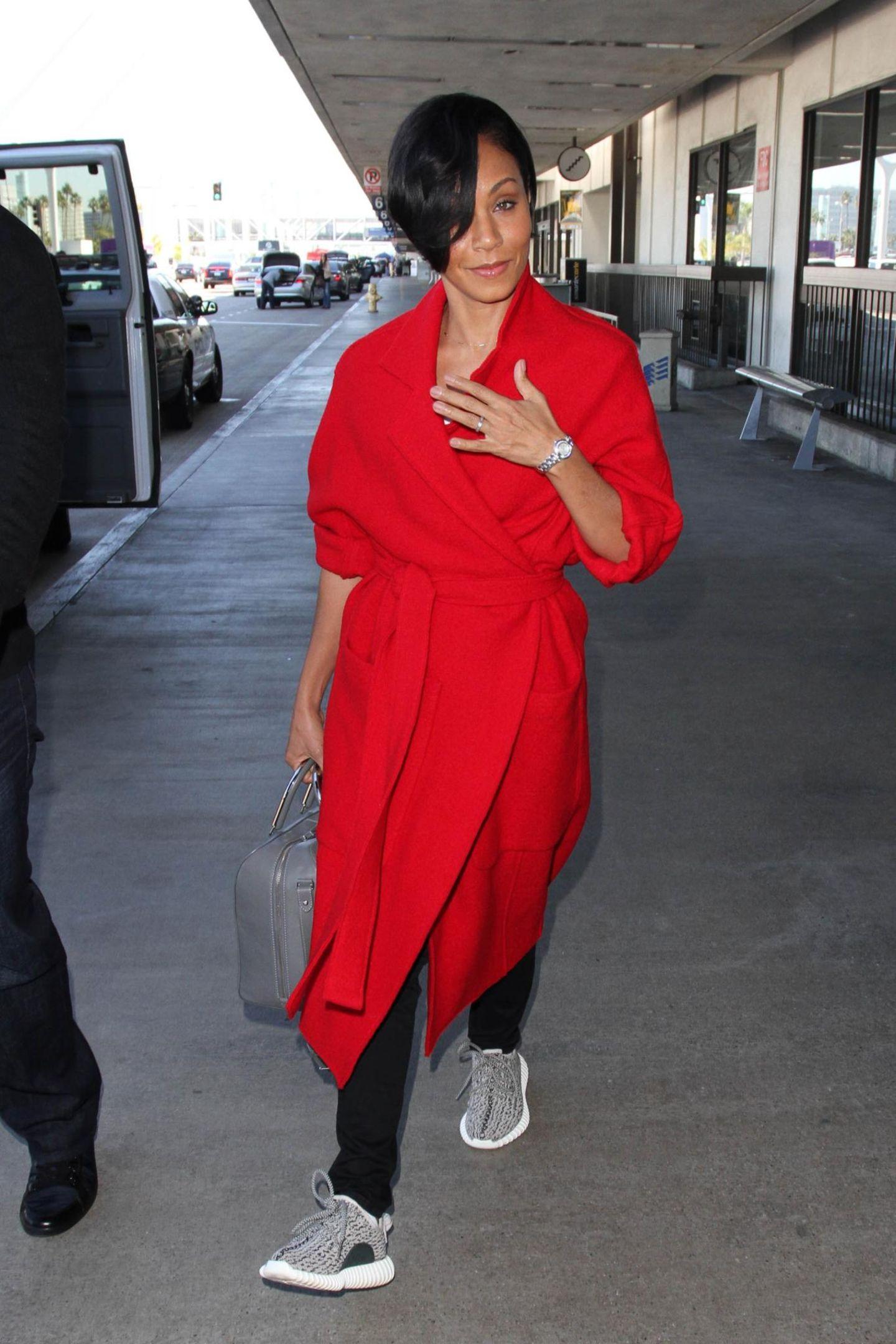 Die charmante Jada Pinkett Smith kommt in einem knallroten Mantel am LAX an.