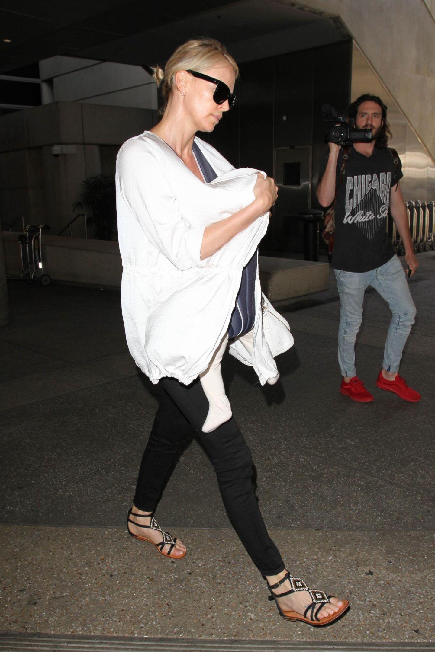 Charlize Theron schützt sich am Flughafen von Los Angeles vor dem Blitzlicht der Paparazzi mit einer großen Sonnenbrille. Auch gut versteckt: Ihre Tochter August.