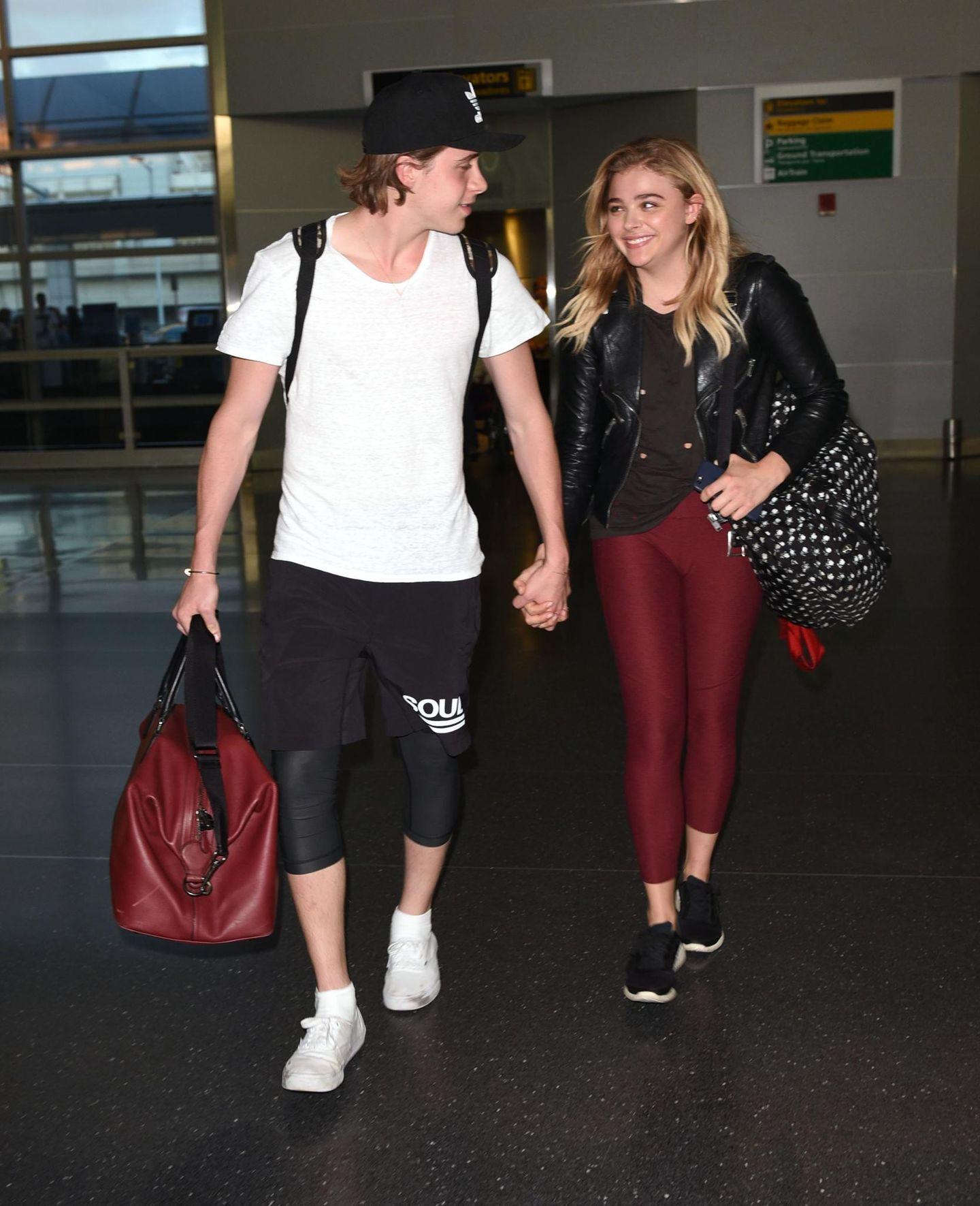 Verliebtsein beflügelt: Trotz des Überseefluges von London nach New York strahlen Brooklyn Beckham und Chloë Moretz.