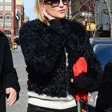 Kate Hudson kombiniert ihre kurze Kunstpelz-Jacke mit Lederhose und auffälliger roter Clutch.