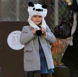 Vom modischen Mini zum lässigen Teenie: Heute posiert Suri mal ganz freundlich mit ihrer kuscheligen Pandamütze zum grauen Wollmantel. Zum Karokleidchen trägt sie schlichte Stiefel.
