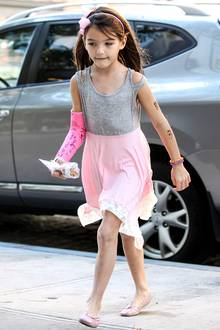 Noch ganz sommerlich im grau-rosa Baumwoll-Kleidchen mit Spitze geht's für Suri mit Mama Katie Holmes in einen Schönheitssalon.