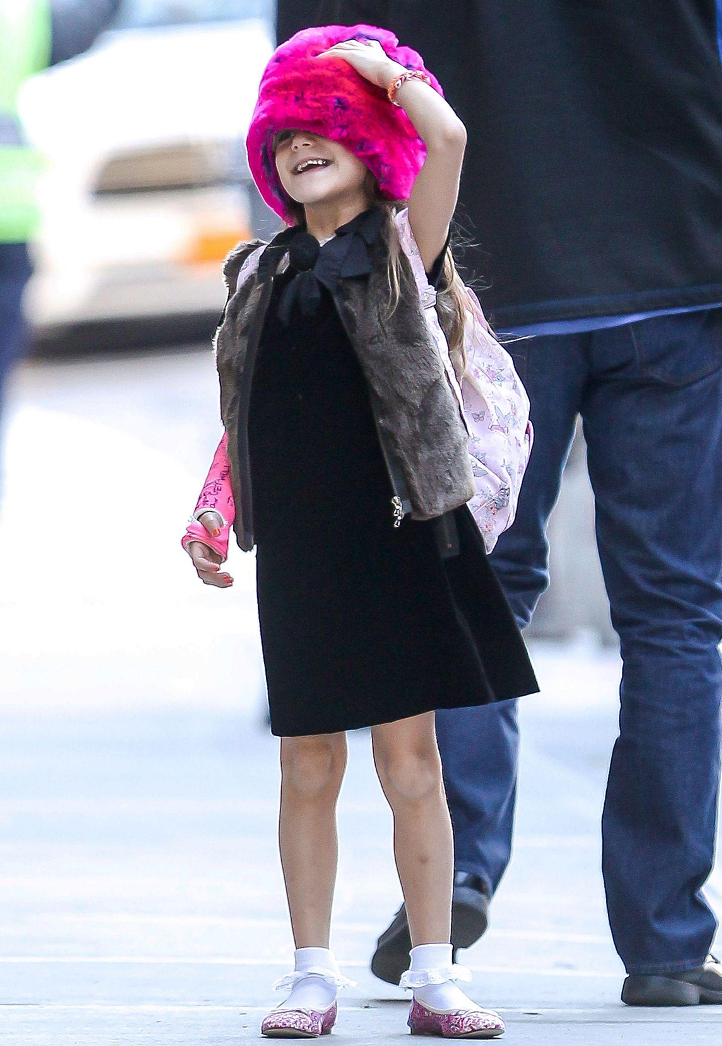 Mit pinker Fellmütze auf dem Kopf und einer Fellweste zum schwarzen Kleid wagt Suri mal ein ganz neues Modeexperiment.
