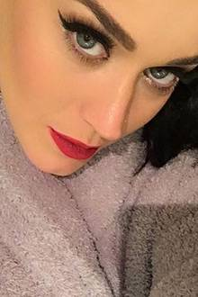 Mit schwungvollem Eyeliner und superlangen Wimpern kuschelt sich Katy Perry in ihren geliebten Frottee-Bademantel.