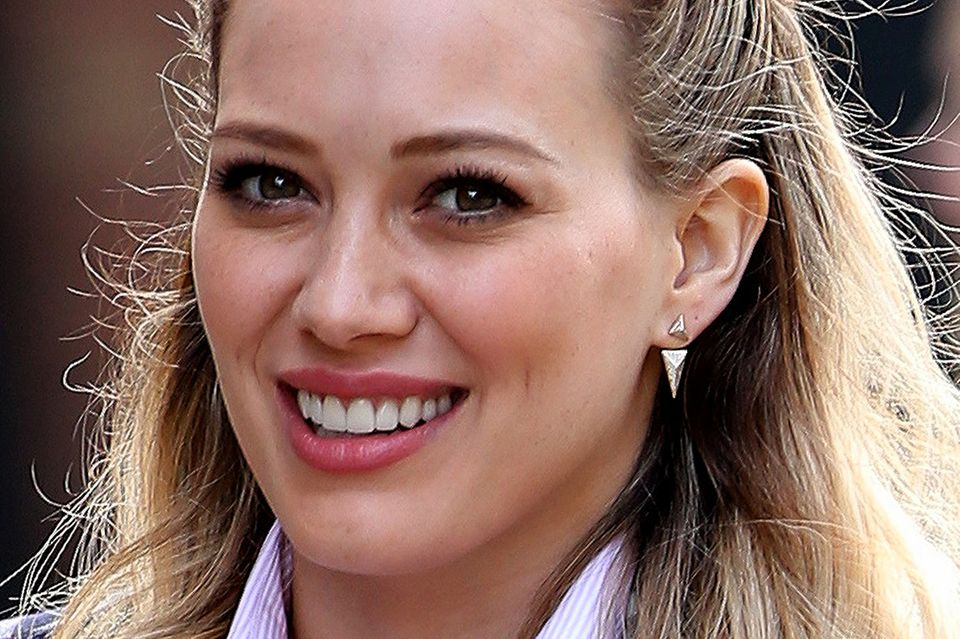 Hilary Duff muss sich dank neues Frisuren-Trends nicht mehr zwischen Zopf und offenem Haar entscheiden. Für den Half-up-Dutt steckt sie ihr Deckhaar hoch und legt ihre leichten Wellen nach vorne über die Schultern.