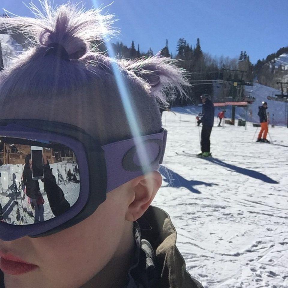 Kelly Osbourne trägt ihr Skioutfit passend zur Haarfarbe .