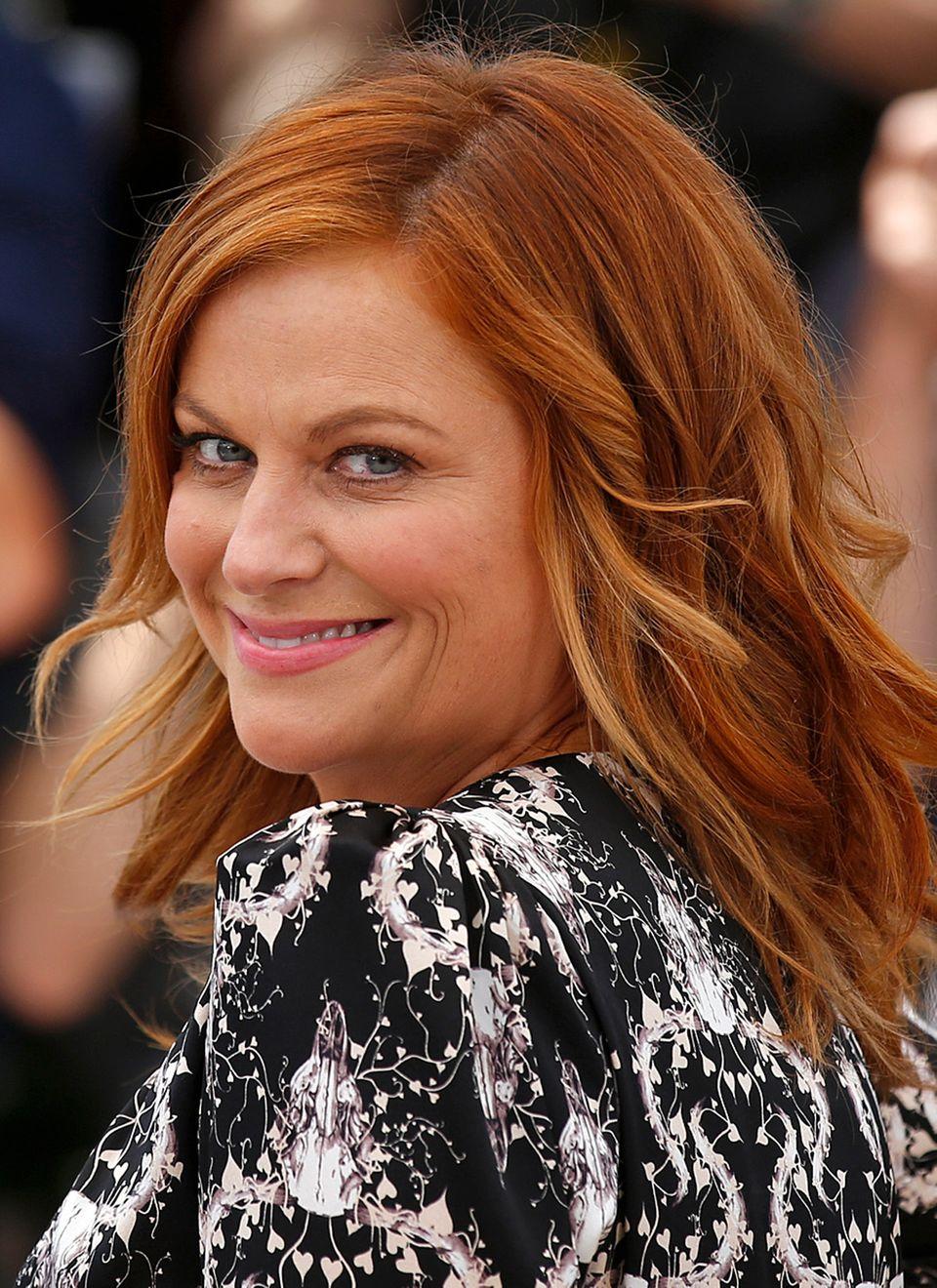 Mit frisch gefärbtem, papayarotem Haar präsentiert sich eine strahlende und eigentlich hellblonde Amy Poehler bei einem Fototermin in Cannes.