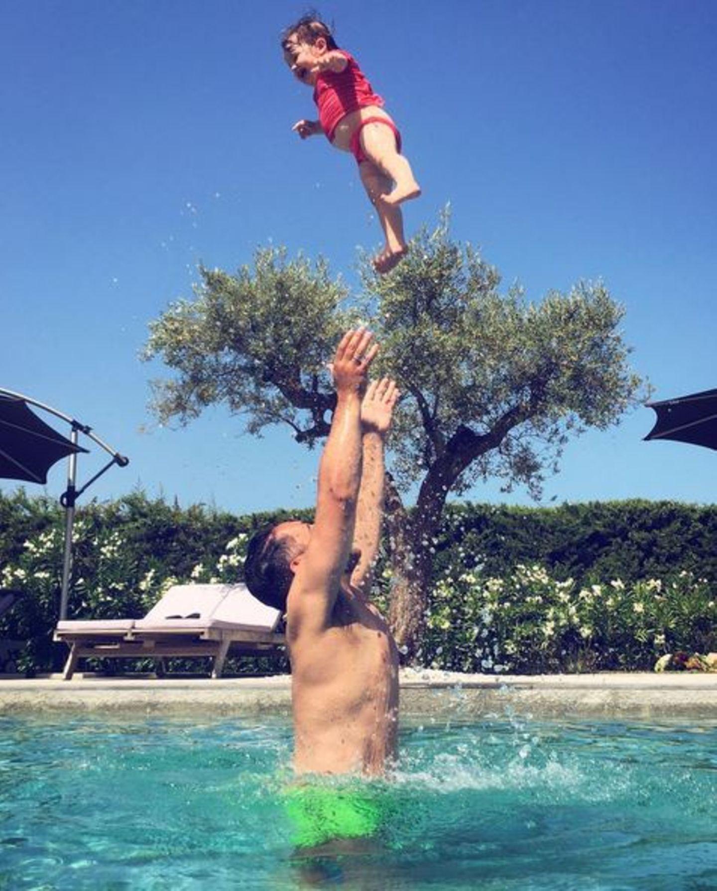 Flieg, Ioni, flieg: James Conran planscht mit Tochter Ioni im Pool und schmeißt sie in die Lüfte. Die Kleine hat dabei sichtlich viel Spaß.
