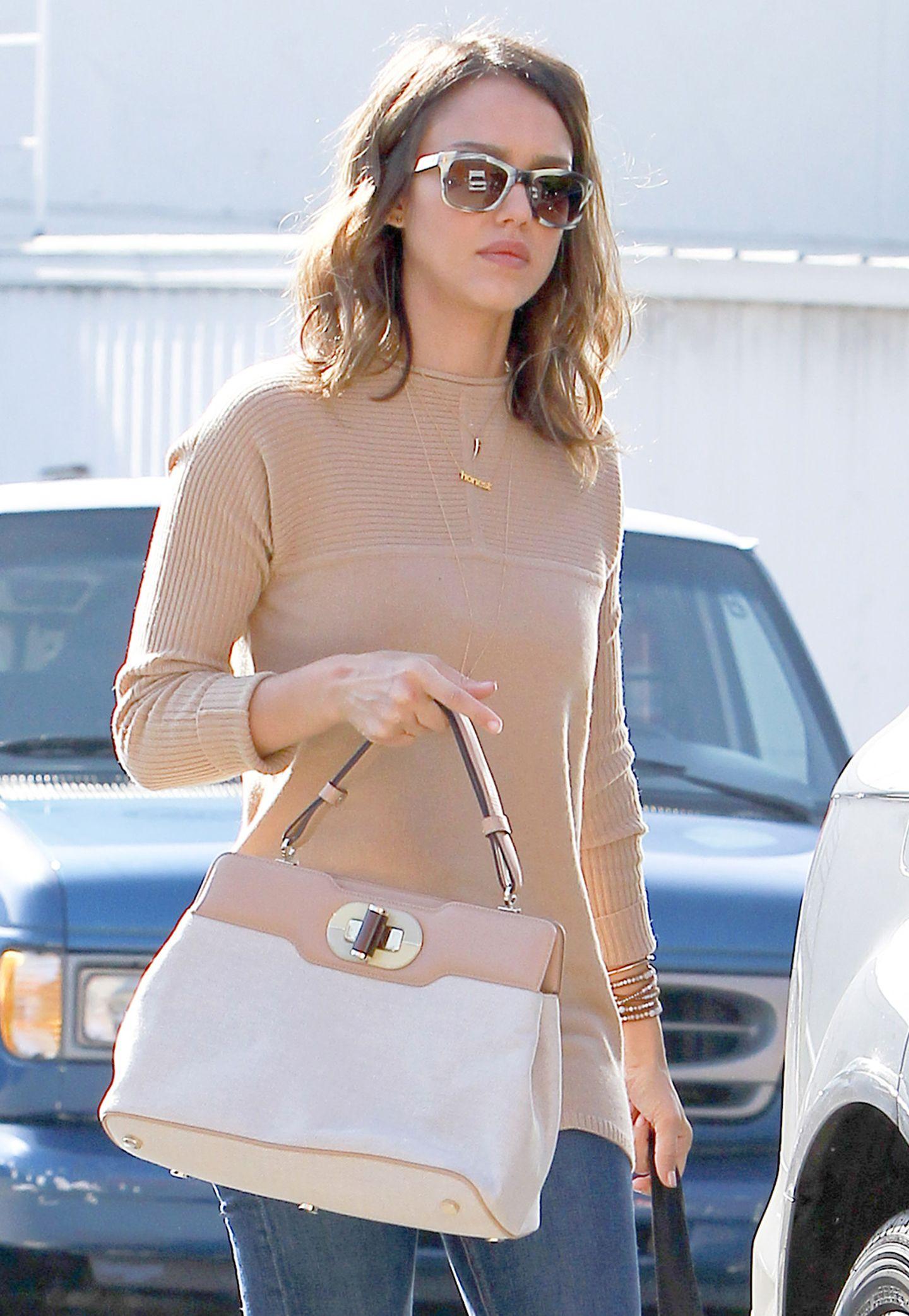 Jessica Alba hat ihre Tasche aus cremeweißem Leinenstoff und camelfarbenem Leder perfekt auf ihren schmalgeschnittenen Pullover abgestimmt.