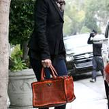 Uma Thurman unterwegs mit ihrer Prada-Tasche aus geflochtenem Kalbsleder. Auch ihre Schleifensandalen stammen vom gleichen Label