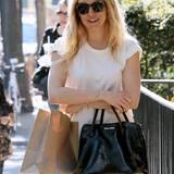 Sienna Miller freut sich über ihre Tasche von Miu Miu.
