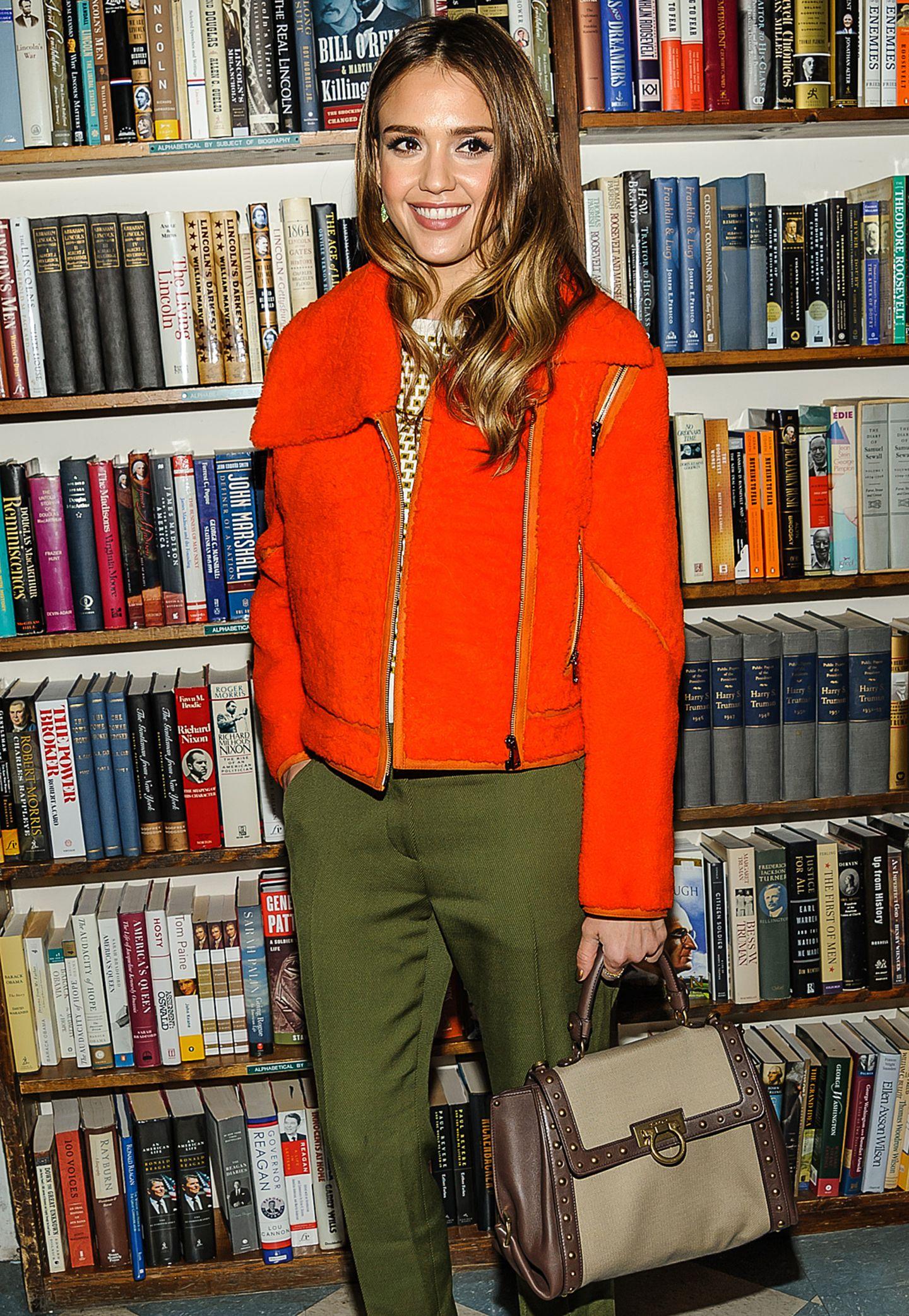 """Bei einer Buchpräsentation trägt Jessica Alba das geräumige Modell """"Sofia"""" aus beigem Canvas mit Leder- und Nietendetails von Salvatore Ferragamo."""
