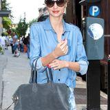 Miranda Kerrs Jeans-Outfit und die blaugraue Wildledertasche passen bestens zusammen.