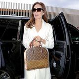 """Das klassische Monogramm-Muster von Angelina Jolies Louis-Vuitton-Tasche wird durch die goldenen Nieten und die roten Nähte schön akzentuiert. Das Modell """"Shopping Bag"""" stammt aus der """"Celebrating Monogram Collection"""" und wurde von Designer Christian Louboutin mitentworfen."""