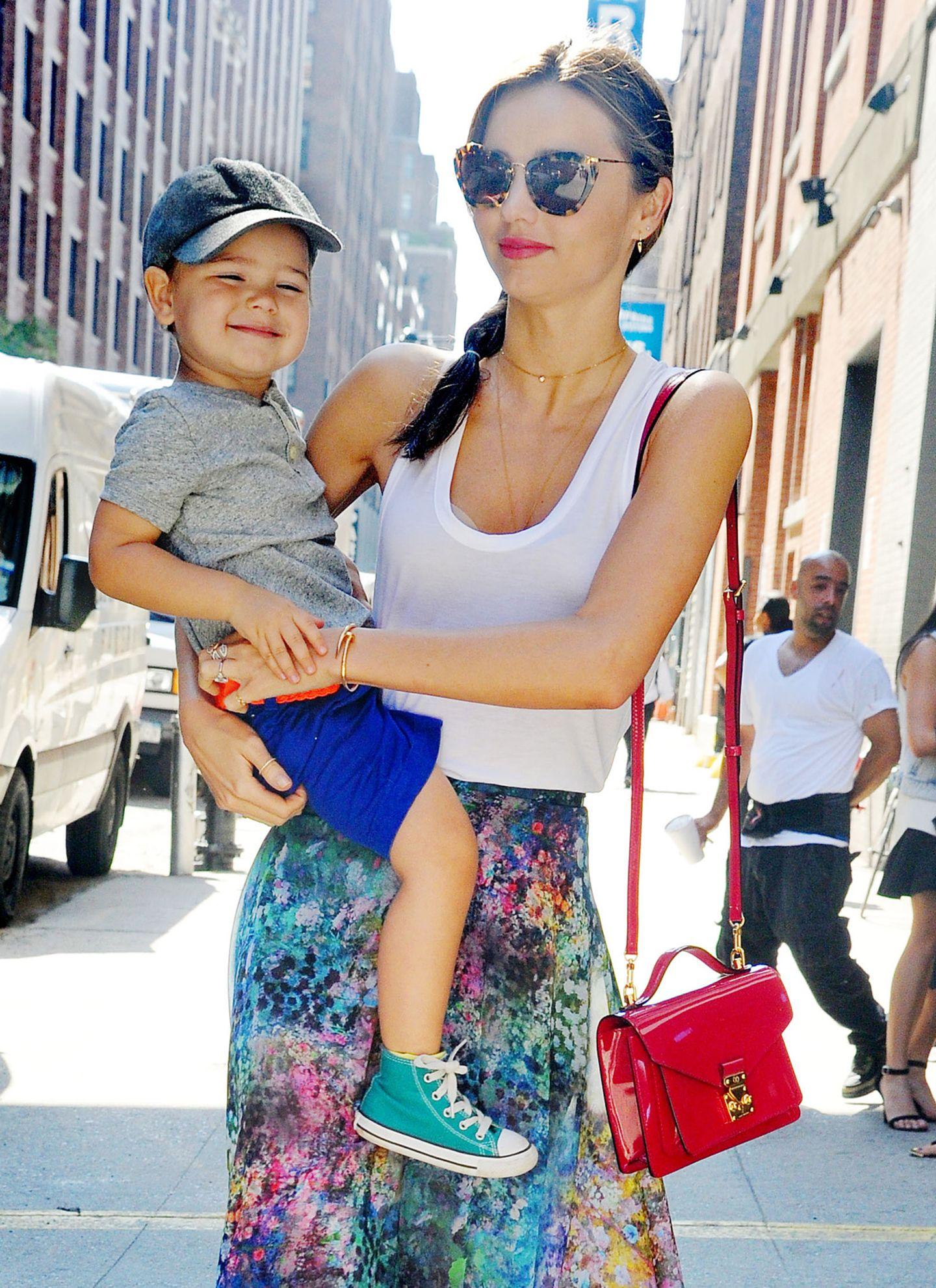 Miranda Kerrs kleine Lacktasche von Louis Vuitton ist ein schönes Accessoire zum bunten, sommerlichen Outfit.