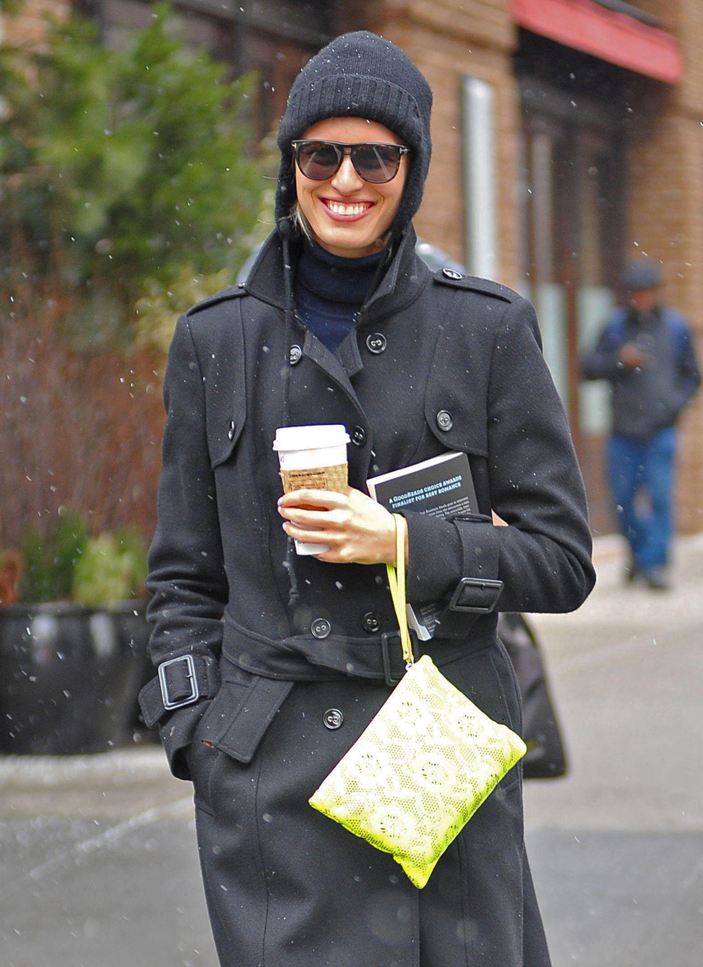 Schwarz gekleidet, aber eine neongelbe Handgelenktasche mit floralem Spitzenbesatz: Karolina Kurkova versteht es, Akzente zu setzen.