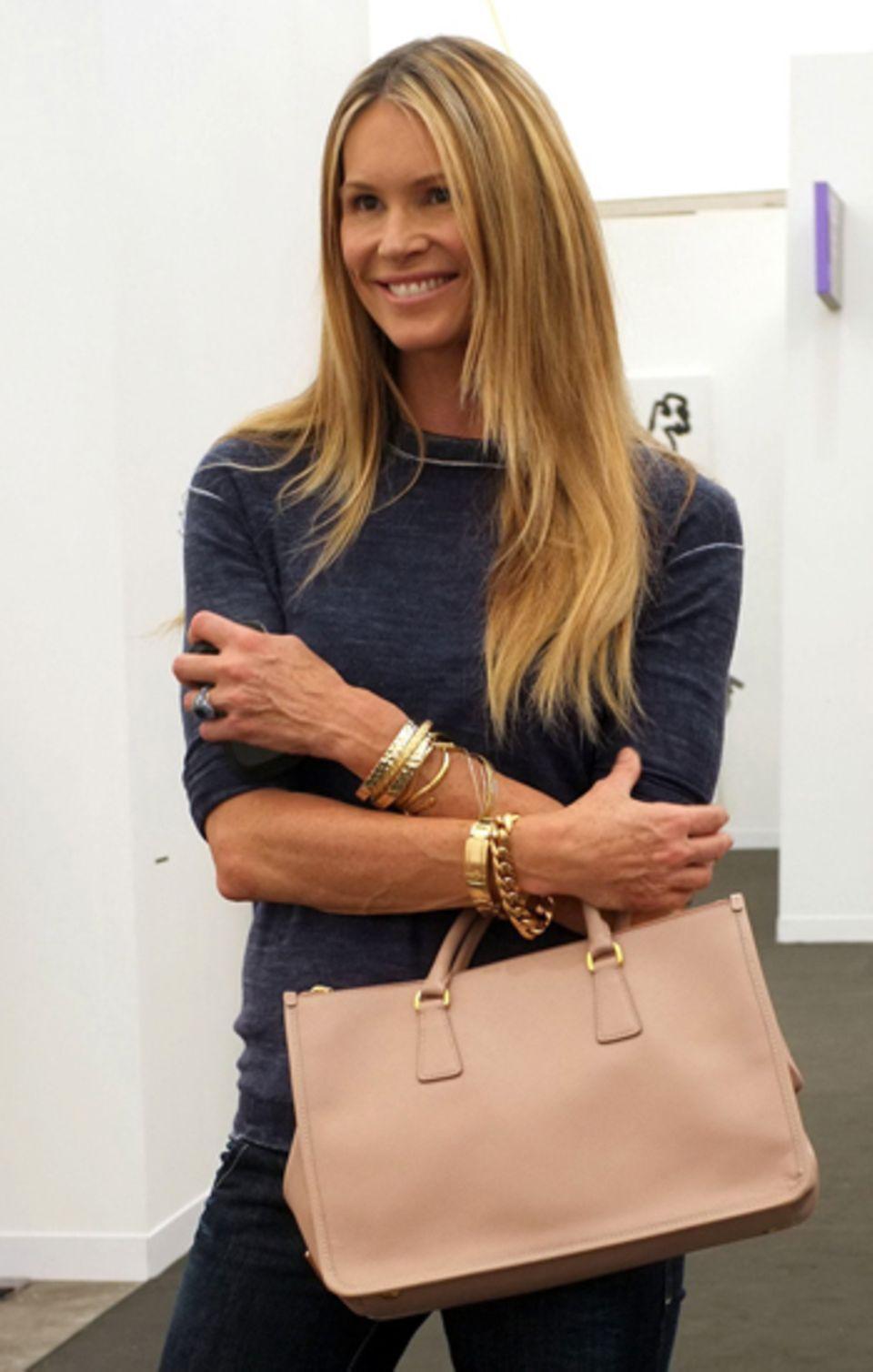 Model Elle Macpherson freut sich über ihre roséfarbene Prada-Tasche. Was sie wohl darin versteckt haben mag?