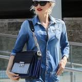 Zum Jeans-Overall trägt Gwen Stefani eine rockige Lederhandtasche mit Tragegurt aus Ketten.
