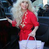 Lady GaGa ist derzeit voll im Versace-Rausch und zeigt erfreut ihre fliederfarbene Tote Bag, die sie zum flatterigen, knallroten Overall trägt.