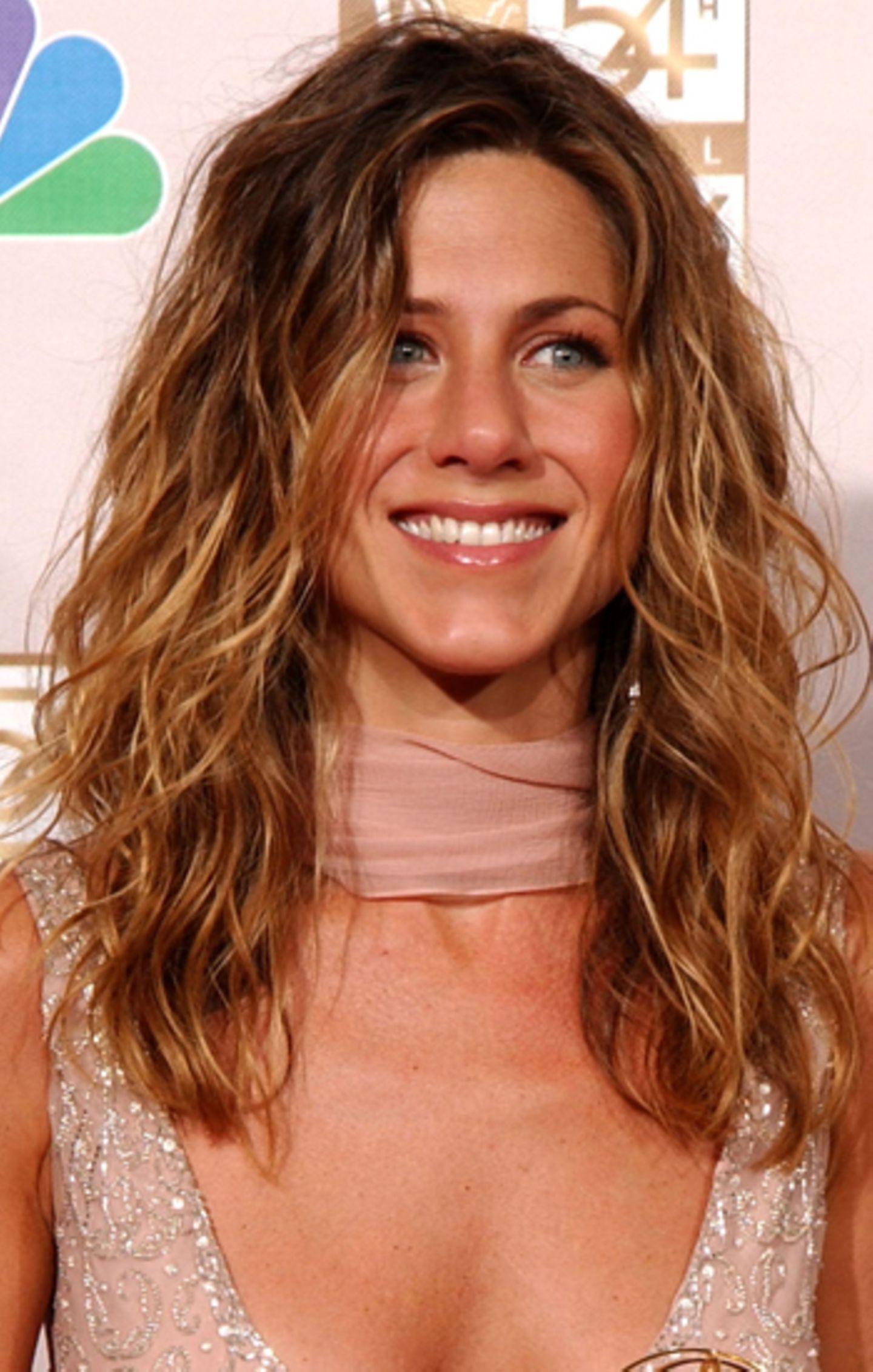 """FEin wenig erblondet und ausgezeichnet mit einem """"Emmy"""" lächelt Aniston 2002 für die Fotografen."""