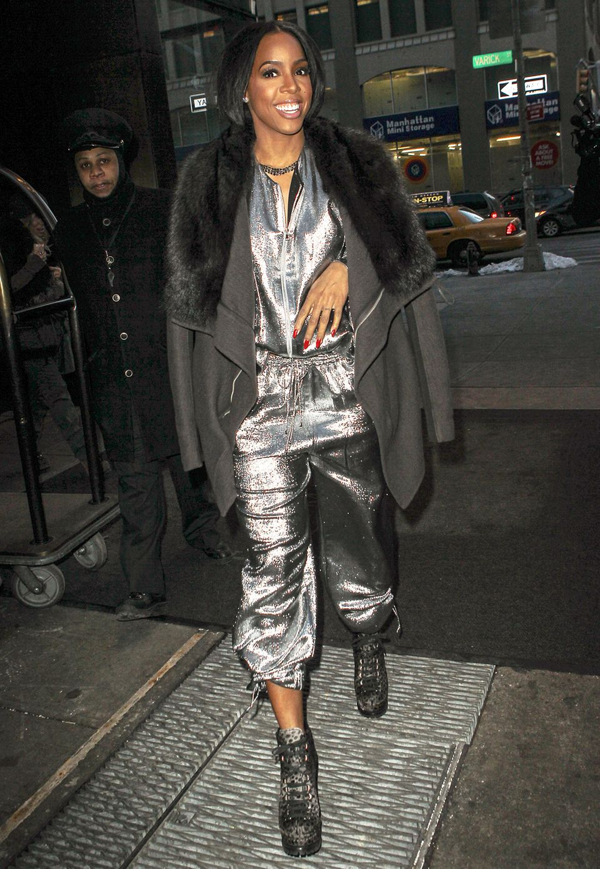 Kelly Rowland kombiniert ihren silbernen Metallic-Overall im Disco-Look mit hohen Plateau-Schnürboots und einer wärmenden grauen Jacke.