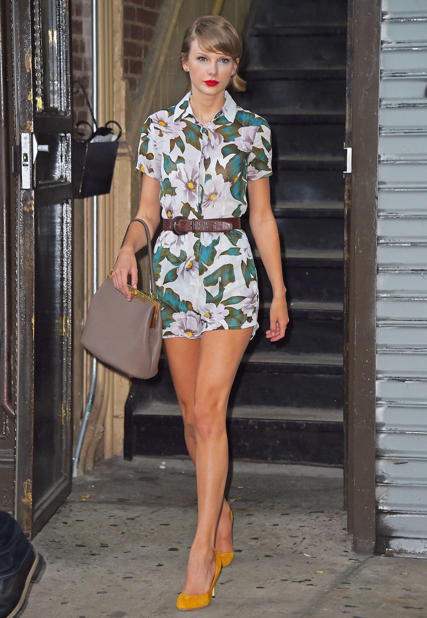 Taylor Swift beherrscht den verspielten Mädchen-Look auf dem Effeff. Das zeigt sie auch mit diesem blumigen Jumpsuit, den sie farblich passend mit gelben Wildleder-Pumps kombiniert.