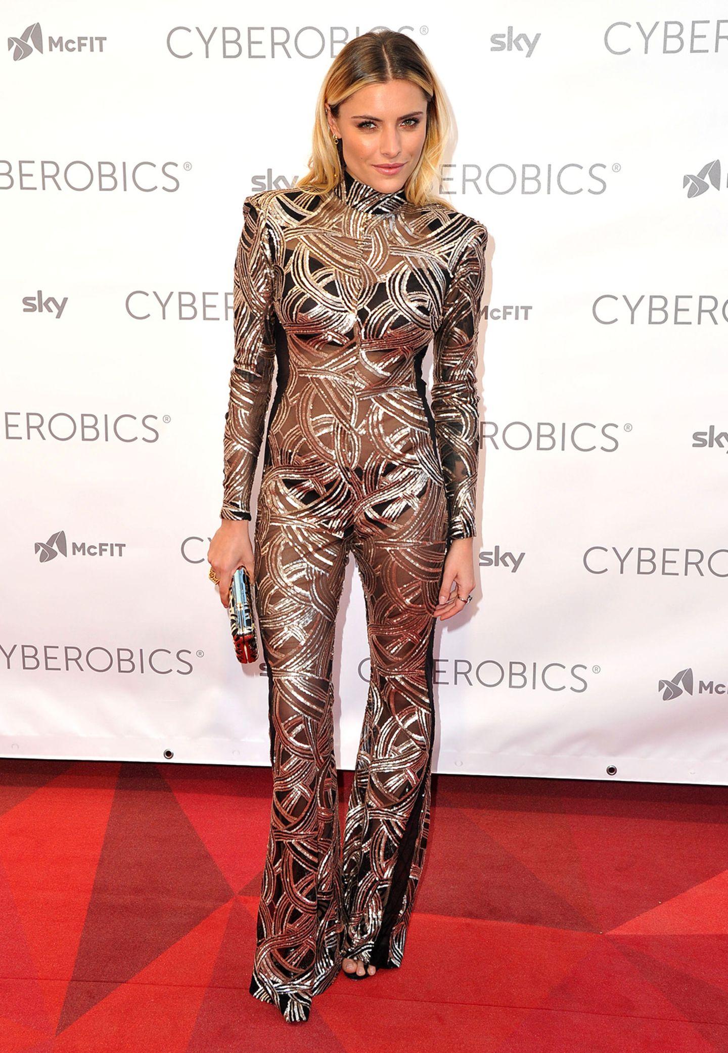 """Sophia Thomallas futuristischer Metallic-Jumpsuit mit viel Durchschein ist sicherlich Geschmackssache, ein Hingucker war sie damit auf dem roten Teppich der Eröffnung des """"World of Cyberobics""""-Sportstudios in Berlin auf jeden Fall."""