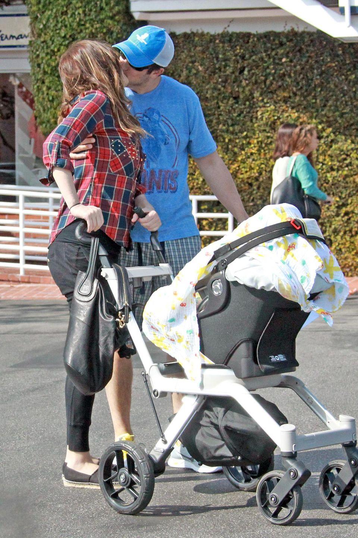 Jason Biggs küsst seine Frau Jenny Mollen zärtlich beim Spaziergang mit dem neu geborenen Söhnchen Sid.