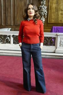 Mit dunkler Marlene-Jeans und rotem Strickpulli über der Polka-Dot-Bluse setzt Salma Hayek voll auf den Retro-Look der 70er.