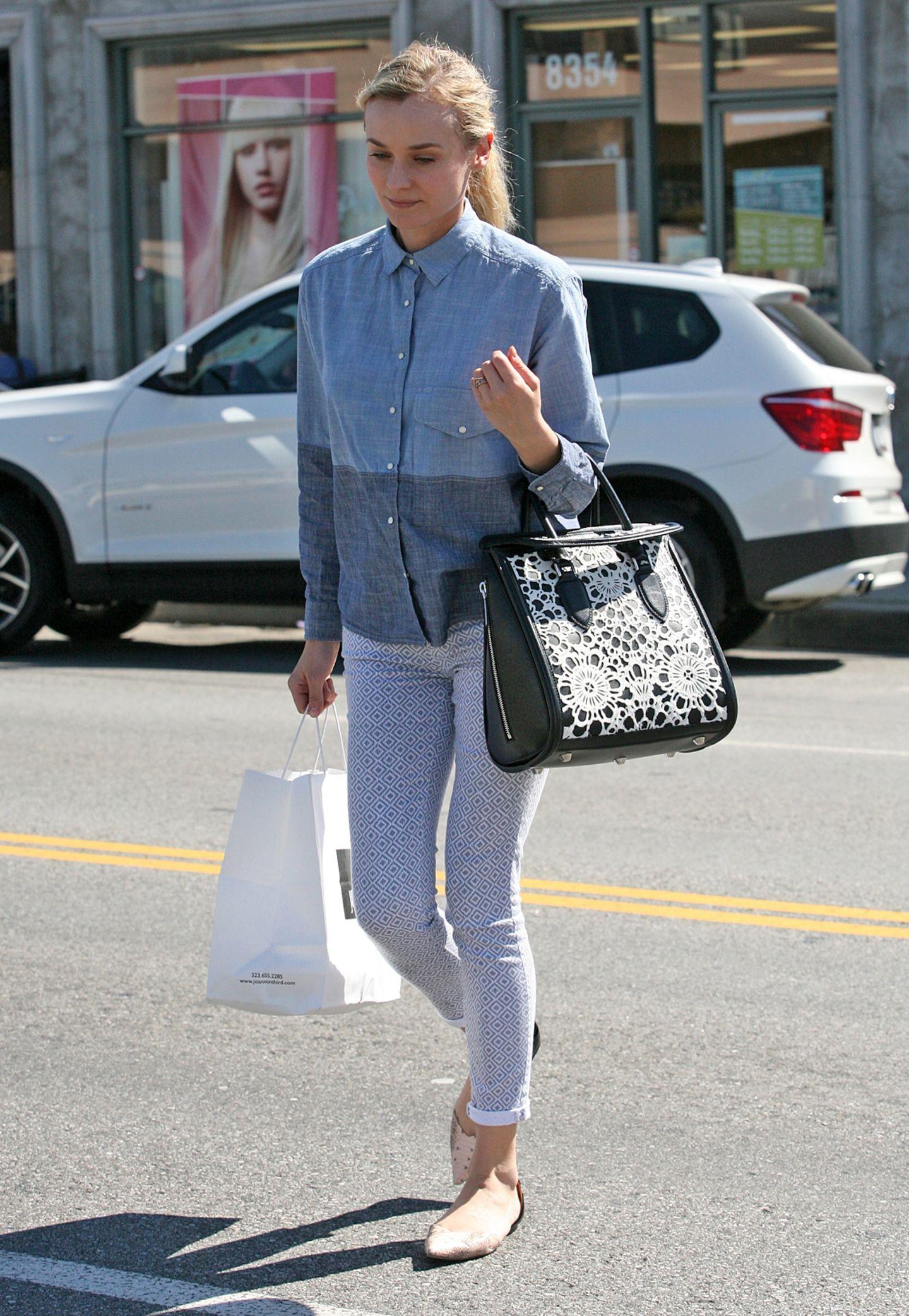 Diane Kruger kombiniert zum zweifarbigen Jeanshemd eine schmale Hose mit Print und flache, spitze Ballerinas.