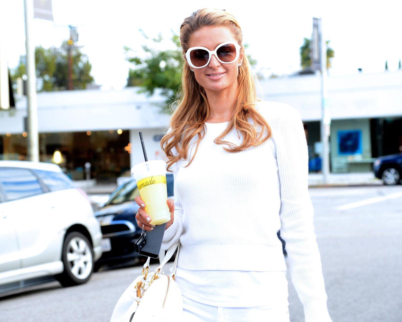 Ganz in Weiß gekleidet ist Paris Hilton mit ihrem Kaltgetränk in Los Angeles unterwegs.