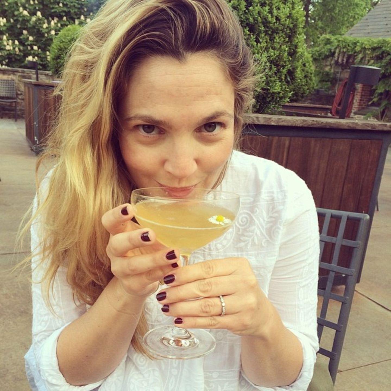 Drew Barrymore freut sich an einem sommerlichen Tag über das Gänseblümchen in ihrem Grtränk.