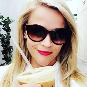 Reese Witherspoon startet ihren Tag mit pinken Lippen, Sonnenbrille und einem Getränk in der Hand.