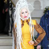 In einem für ihre Verhältnisse sehr eleganten, senfgelben Outfit zeigt sich Lady GaGa vor einem Londoner Hotel. Das auffällige Midikleid mit ausgestelltem Saum fällt besonders durch den weißen Stehkragen und die mit Metallstäbchen besetzten Ärmel auf.