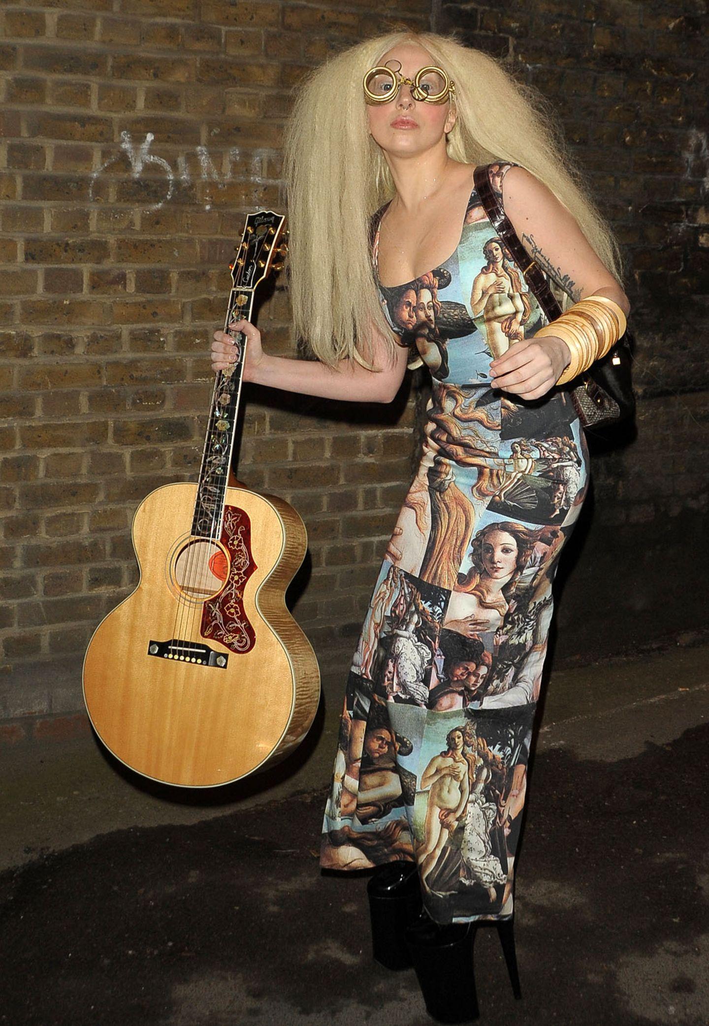 """Auf den Spuren von Botticellis Venus und Harry Potters """"Professor Trelawny"""" stakst Lady GaGa samt Gitarre aus ihrem Londoner Hotel."""