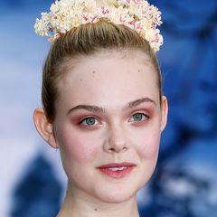 """""""Maleficent""""-Star Elle Fanning präsentiert nicht nur ein avantgardistisches Augen-Make-up, sondern unterstreicht ihren elfengleichen Look auch mit zartgelben Kunstblumen in ihrer Hochsteckfrisur."""