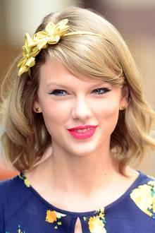 Zwei goldgelbe Seidenblüten auf dem Haarreifen unterstreichen Taylor Swifts frühlingshaften Look.