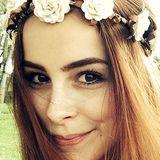 Lena Meyer-Landrut schmückt sich mit einem Blumenbesetzten Band in Braun und Creme, das sie über dem offenen Haar trägt.