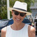 Passend zum schlichten Sommerkleid wählt Minnie Driver einen luftigen weißen Hut mit breiter Krempe.