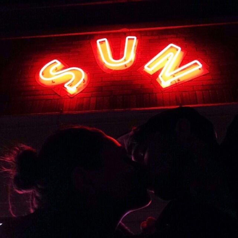 """Dezember 2013  Ashton Kutcher küsst Freundin Mila Kunis und kommentiert dies mit dem Wort """"Sunset""""."""