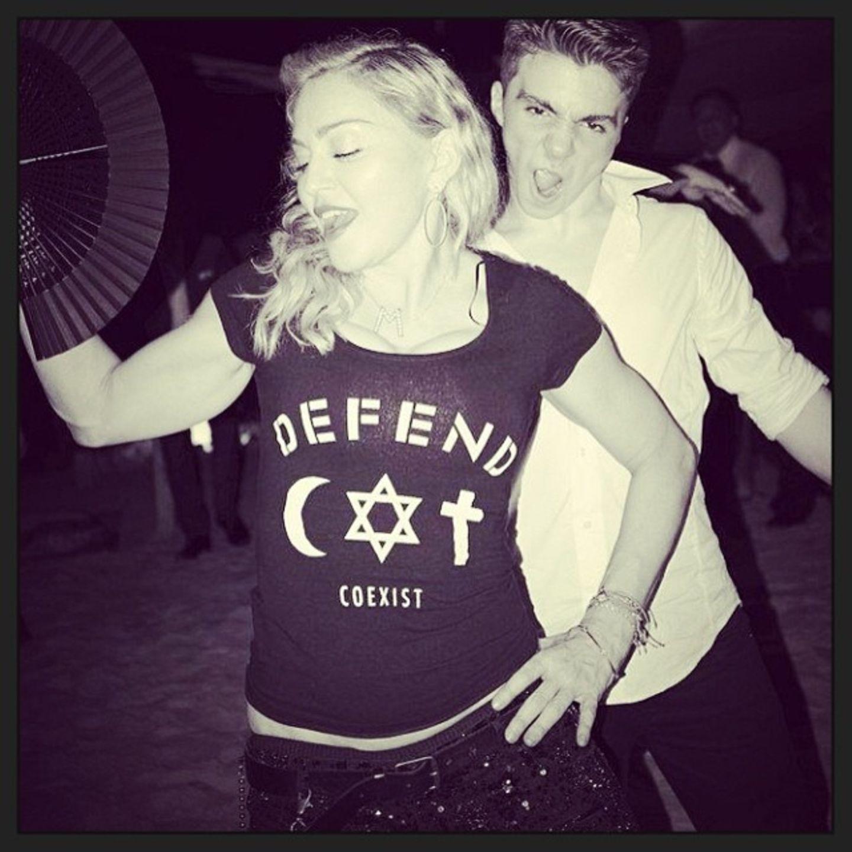 Dezember 2013  Madonna und Sohn Rocco feiern am Strand von Haiti, dabei trägt sie ein Shirt ihrer eigenen Kollektion.