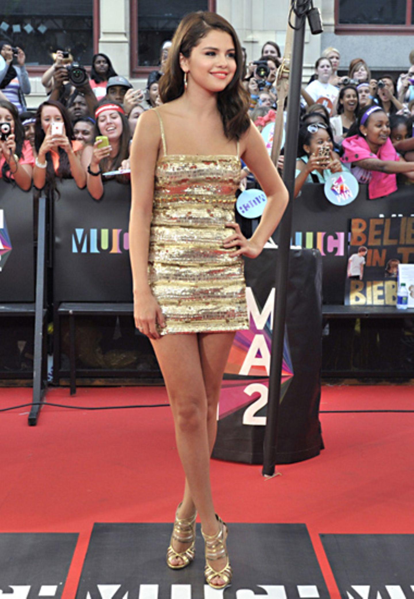 Selena Gomez glänzt in diesem gestreiften Supermini-Dress (Roberto Cavalli) mit passenden High Heels wie ein Goldmariechen.