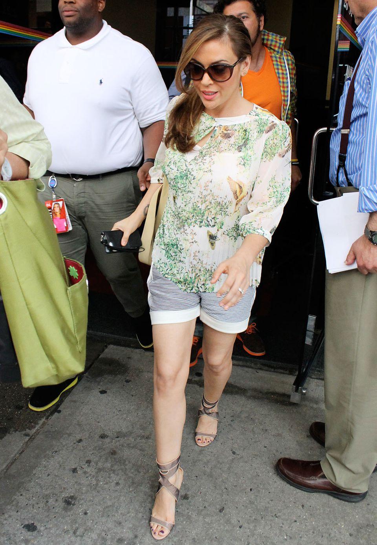 Alyssa Milano wählt zum sommerlich bedruckten Chiffon-Shirt eine maritim gestreifte Shorts aus Jersey.
