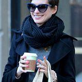 Den schwarzen Strickschal trägt Anne Hathaway wie einen Knoten um ihren Hals.