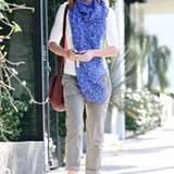 Emily Blunt trägt einen leuchtend blauen Schal mit kleinen Blümchen und wertet so das komplette Outfit auf.